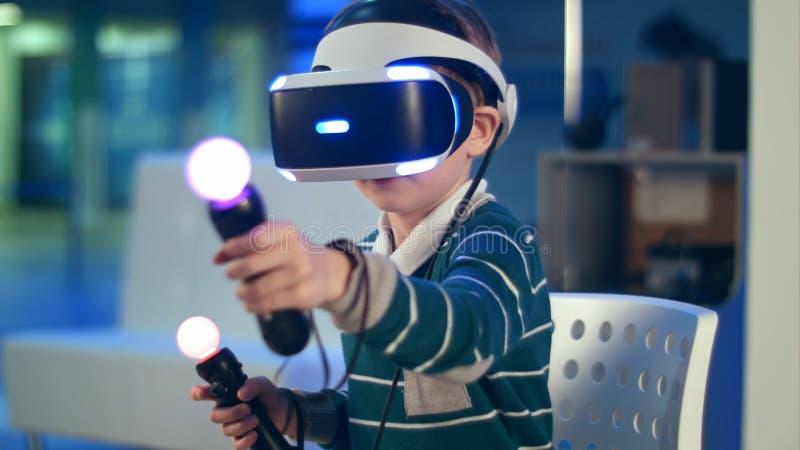 Rapaz pequeno com os controladores do movimento da realidade virtual que têm a experiência immersive do jogo imagens de stock royalty free