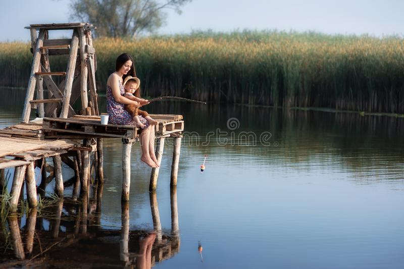 Rapaz pequeno com pesca da mãe no lago imagem de stock