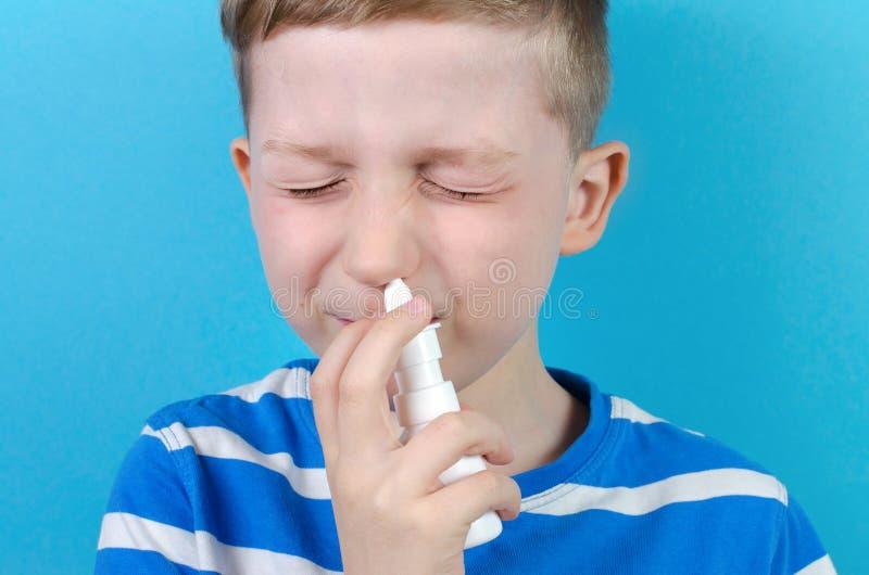 Rapaz pequeno com pulverizador nasal, fundo azul imagem de stock