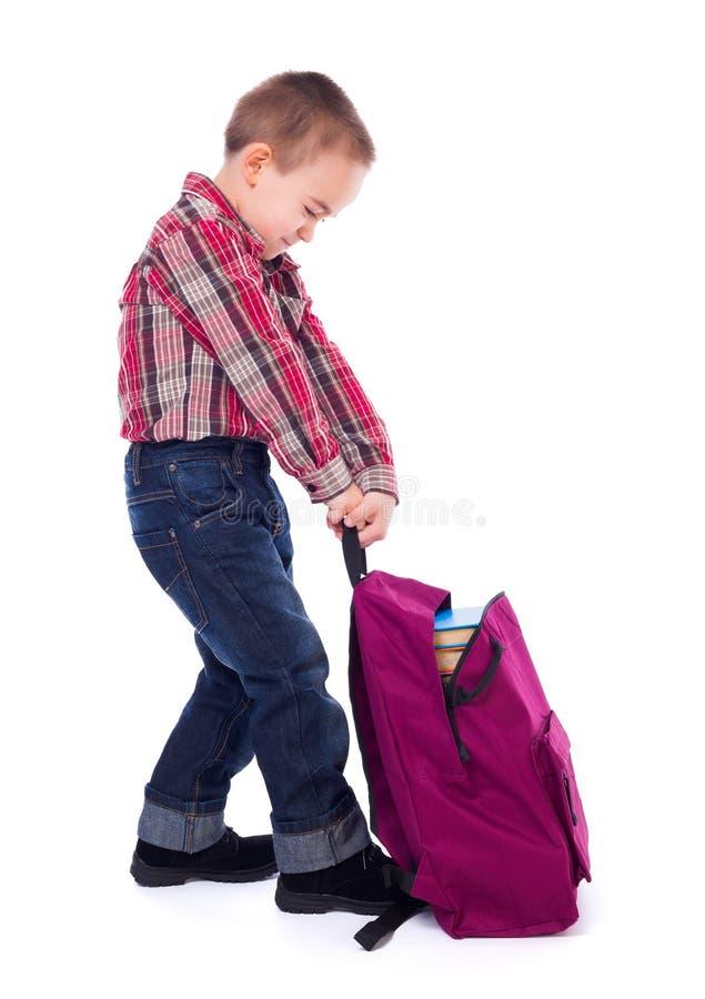 Rapaz pequeno com schoolbag pesado fotos de stock royalty free