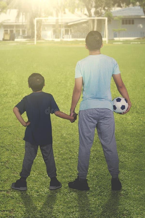 Rapaz pequeno com seu pai que guarda a bola de futebol imagens de stock royalty free