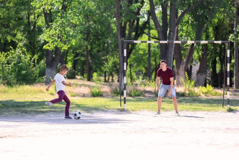 Rapaz pequeno com seu paizinho que joga o futebol no passo do futebol imagens de stock