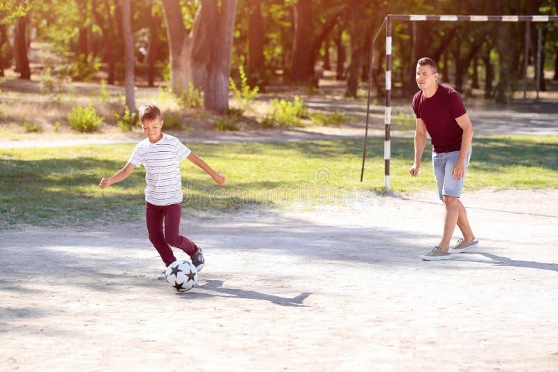 Rapaz pequeno com seu paizinho que joga o futebol no passo do futebol fotos de stock royalty free