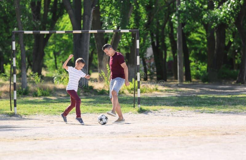 Rapaz pequeno com seu paizinho que joga o futebol no passo do futebol fotografia de stock