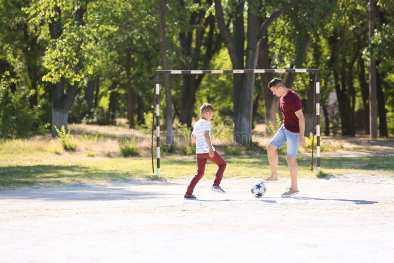 Rapaz pequeno com seu paizinho que joga o futebol no passo do futebol imagem de stock royalty free