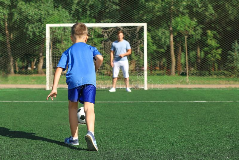 Rapaz pequeno com seu paizinho que joga o futebol no passo do futebol foto de stock royalty free