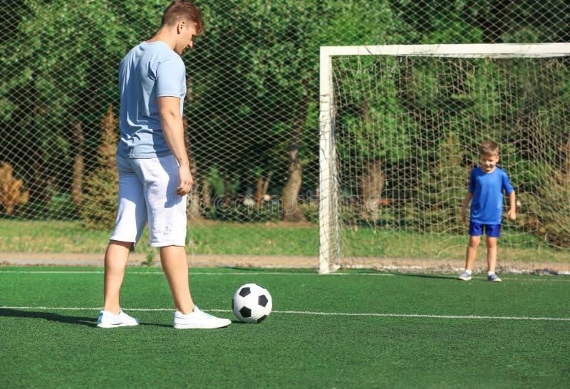 Rapaz pequeno com seu paizinho que joga o futebol no passo do futebol imagem de stock