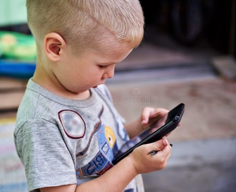 Rapaz pequeno com smartphone imagem de stock