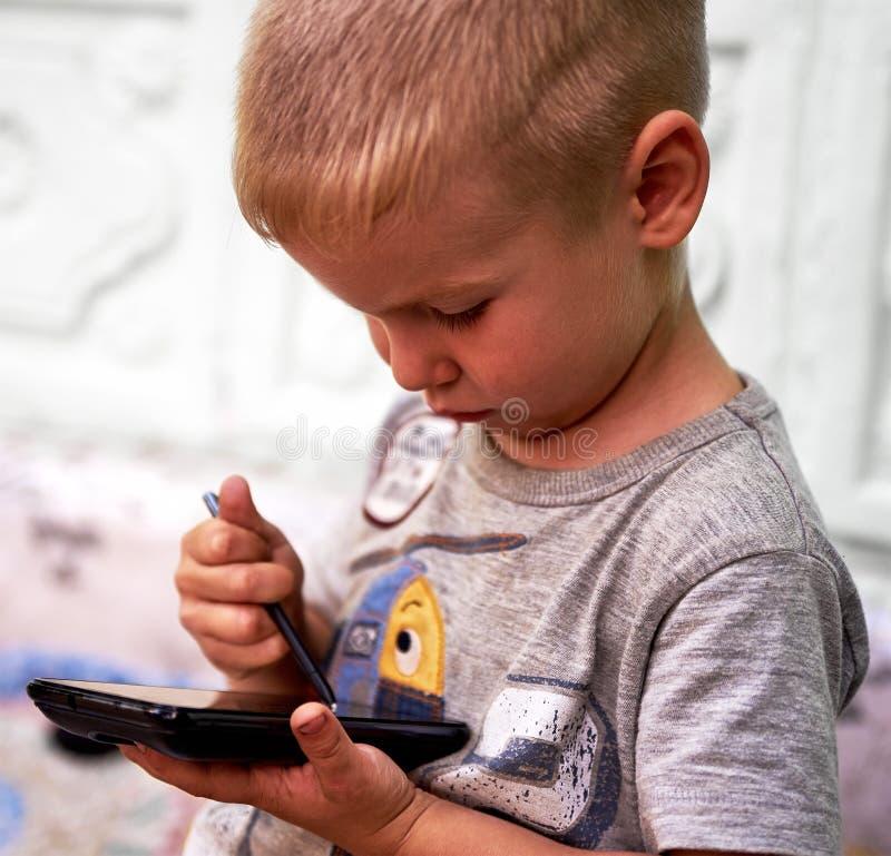 Rapaz pequeno com smartphone fotos de stock