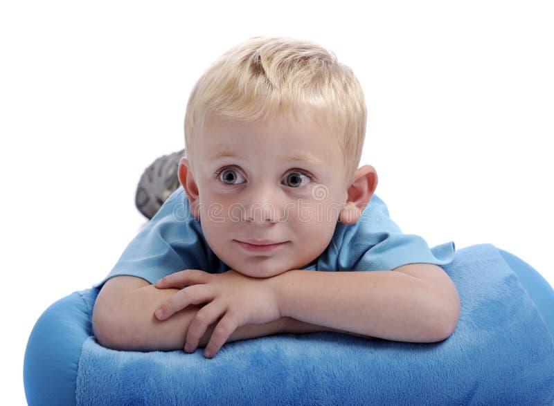 Rapaz pequeno com sua cabeça que descansa em seus braços imagens de stock royalty free
