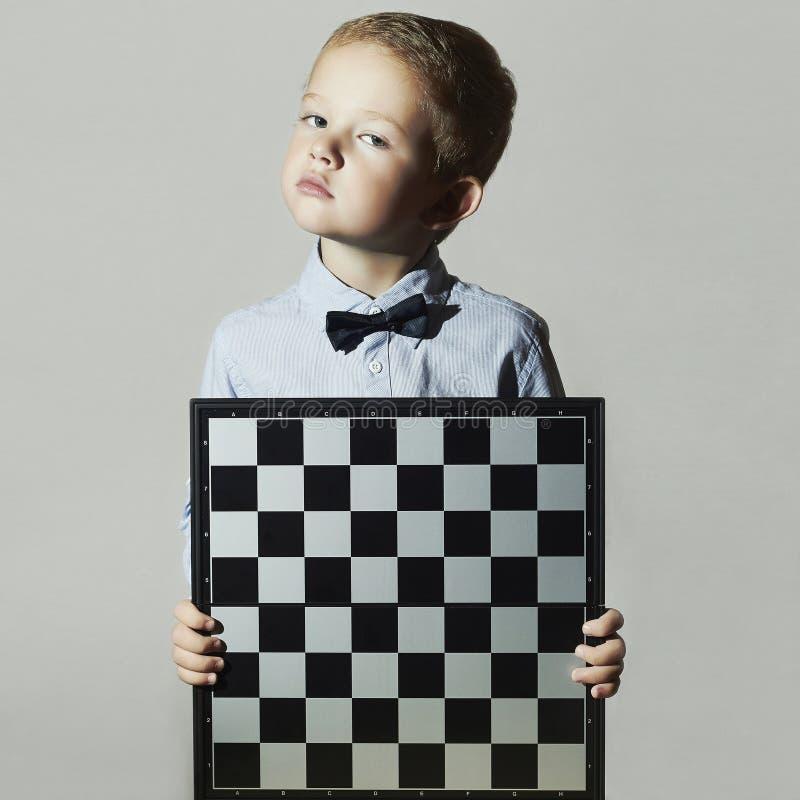 Rapaz pequeno com tabuleiro de xadrez Criança pequena do gênio fotografia de stock