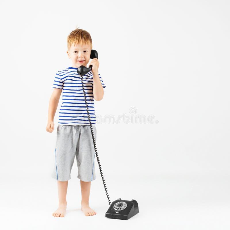 Rapaz pequeno com telefone retro contra um branco imagem de stock
