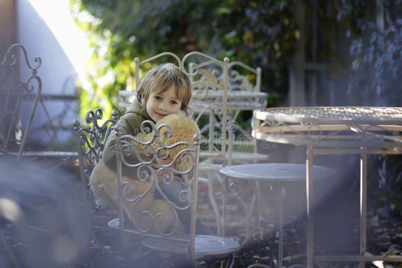 Rapaz pequeno com um urso de peluche que senta-se na cadeira fotos de stock royalty free