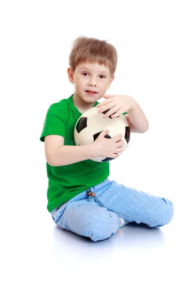 Rapaz pequeno com uma bola de futebol imagem de stock