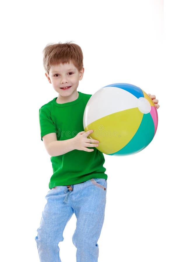 Rapaz pequeno com uma bola listrada fotografia de stock