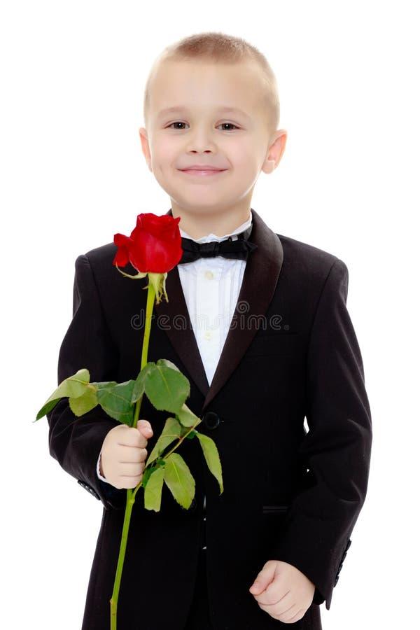 Rapaz pequeno com uma flor da rosa foto de stock royalty free