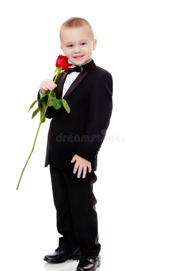 Rapaz pequeno com uma flor da rosa imagem de stock