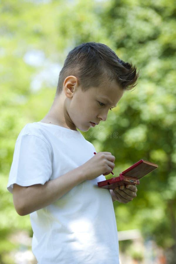 Rapaz pequeno com videogame handheld ao ar livre imagem de stock