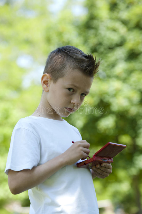 Rapaz pequeno com videogame handheld ao ar livre imagens de stock royalty free