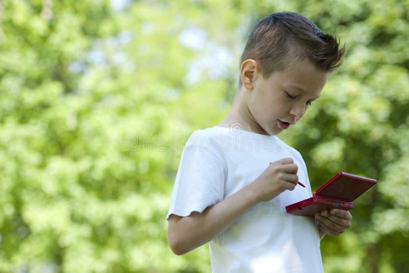 Rapaz pequeno com videogame handheld ao ar livre fotos de stock royalty free