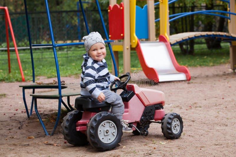 Rapaz pequeno da criança que joga no campo de jogos e que conduz um carro fotografia de stock