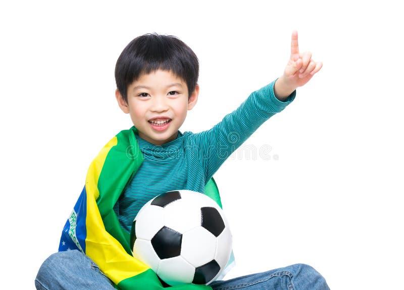 Rapaz pequeno de Ásia com bandeira de Brasil e bola de futebol fotografia de stock royalty free