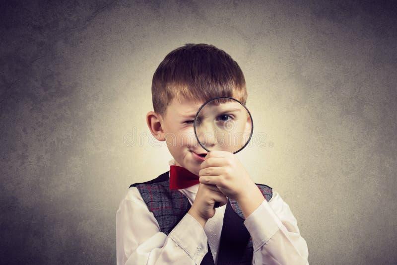 Rapaz pequeno de exploração curioso com lupa, em vagabundos amarelos fotos de stock royalty free