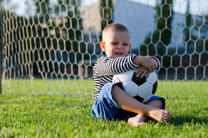 Rapaz pequeno de riso com seu futebol imagens de stock royalty free