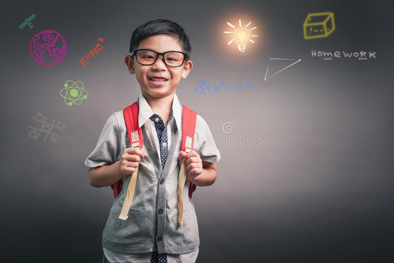 Rapaz pequeno de sorriso alegre com trouxa grande olhando a c?mera Conceito da escola De volta ? escola fotos de stock royalty free