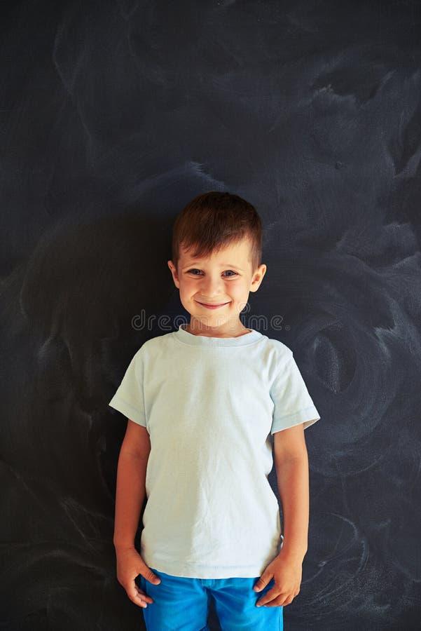 Rapaz pequeno de sorriso bonito que está contra o quadro-negro da escola foto de stock royalty free