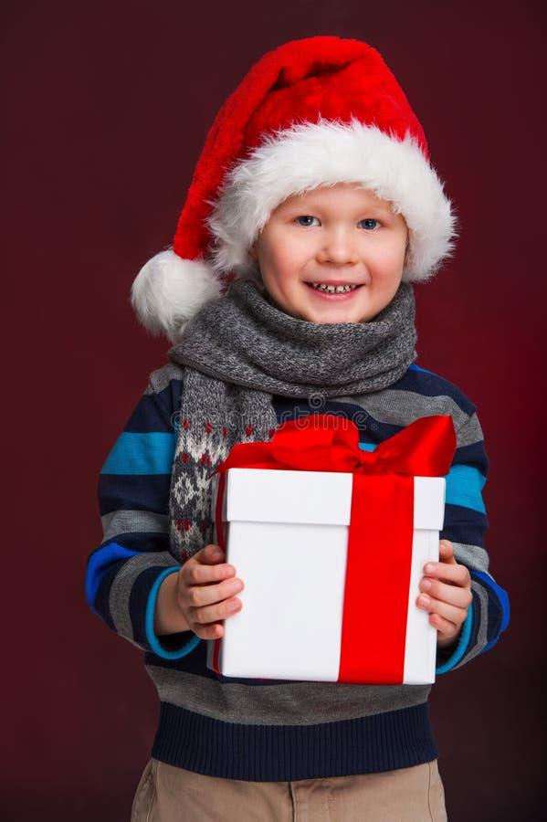 Rapaz pequeno de sorriso com o presente do Natal em sua mão. imagem de stock royalty free