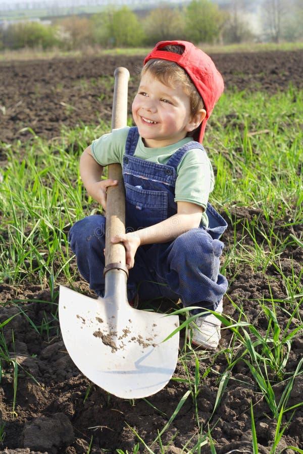 Rapaz pequeno de sorriso com pá grande imagens de stock royalty free