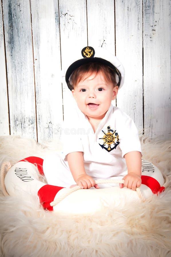Rapaz pequeno de sorriso engraçado vestido como um capitão de mar no tampão naval fotografia de stock royalty free