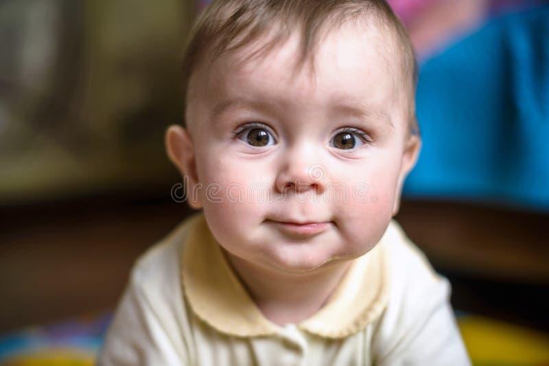 Rapaz pequeno de sorriso feliz bonito com olhos azuis grandes e pestanas longas que surpreendem Foco seletivo sobre fotografia de stock royalty free