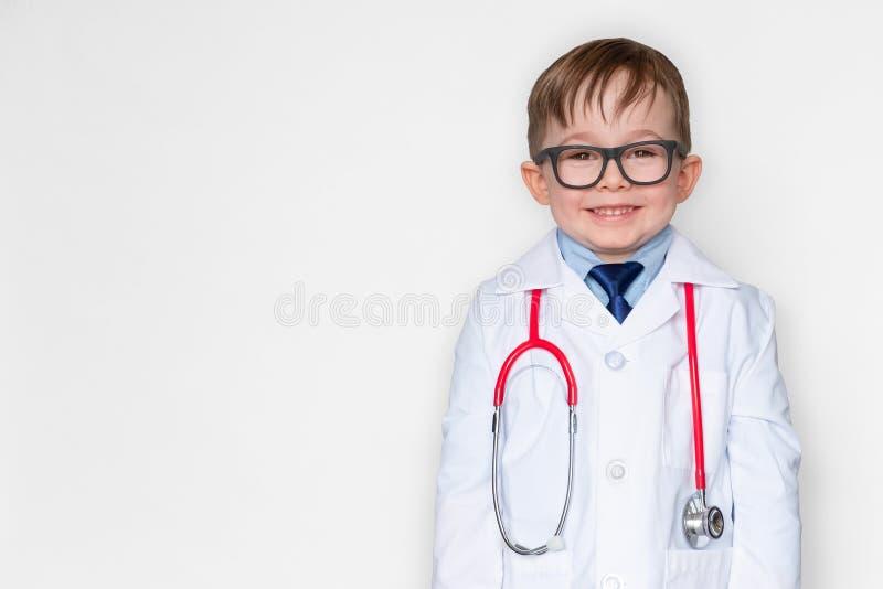 Rapaz pequeno de sorriso no uniforme médico que veste um estetoscópio e a vista da câmera no branco imagem de stock royalty free