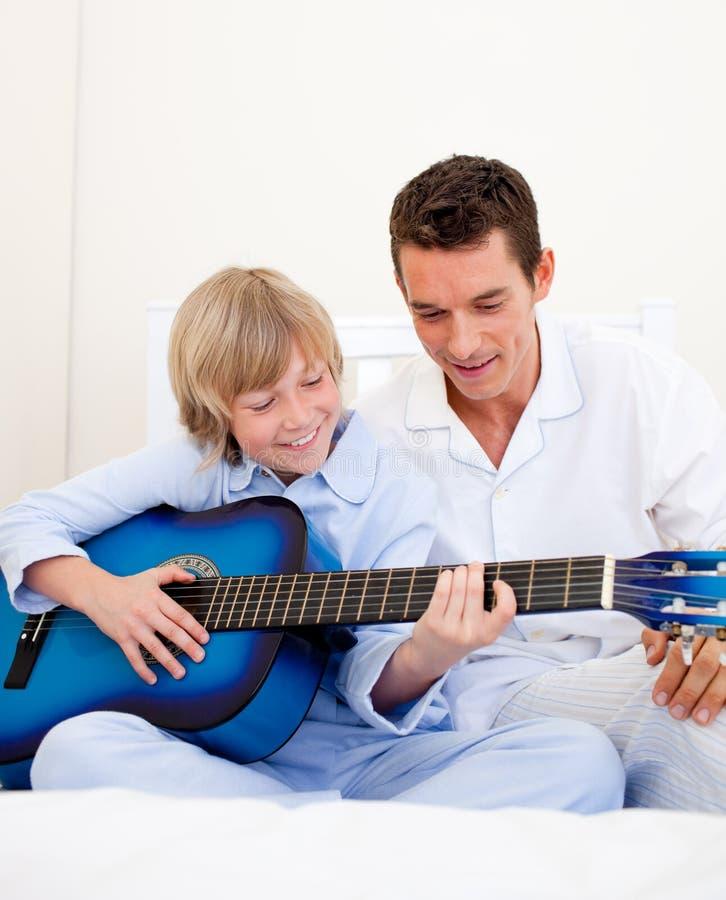 Rapaz pequeno de sorriso que joga a guitarra com seu pai foto de stock royalty free