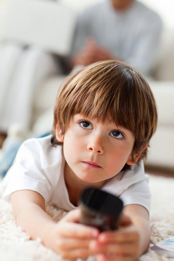 Rapaz pequeno de sorriso que prende um telecontrole fotos de stock