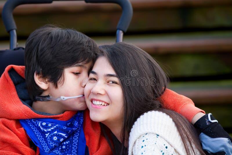 Rapaz pequeno deficiente que beija sua irmã mais velha no mordente fotografia de stock
