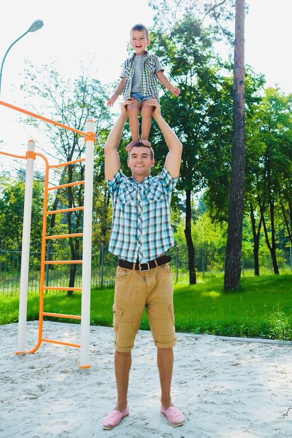 Rapaz pequeno desportivo feliz que está em meu father& x27; ombros de s fotos de stock royalty free