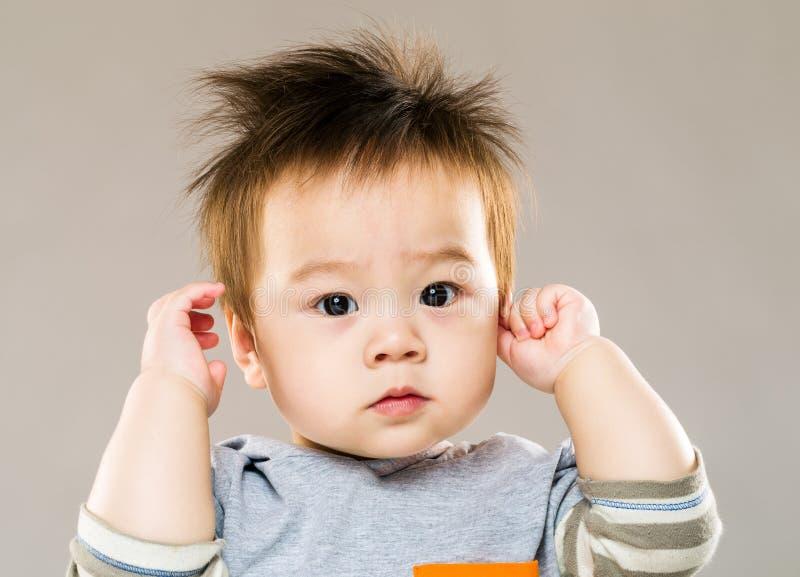 Rapaz pequeno doce com a orelha do toque da mão fotografia de stock royalty free