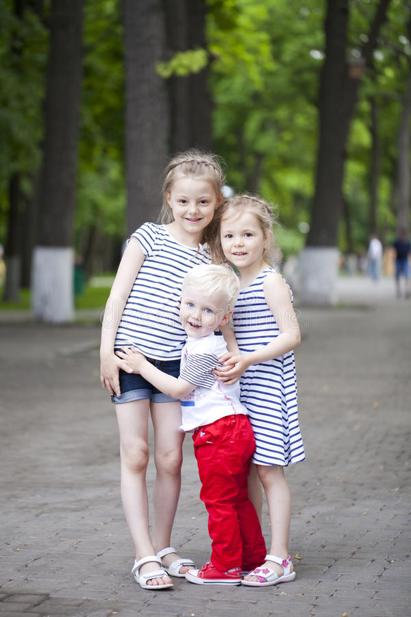 Rapaz pequeno e dois primos mais idosos, encontrando-se no parque do verão fotos de stock royalty free