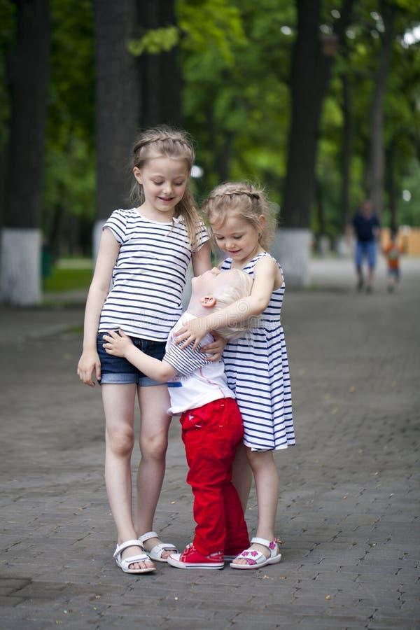 Rapaz pequeno e dois primos mais idosos, encontrando-se no parque do verão fotografia de stock royalty free
