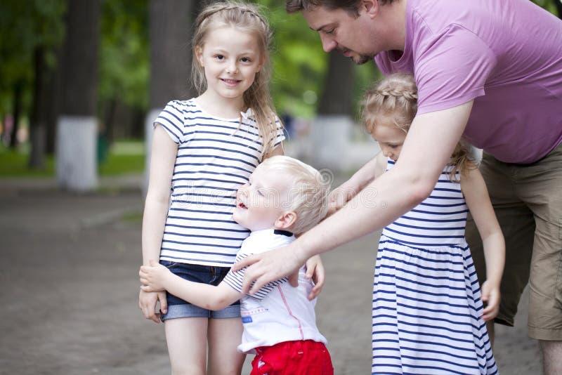 Rapaz pequeno e dois primos mais idosos, encontrando-se no parque do verão imagens de stock royalty free