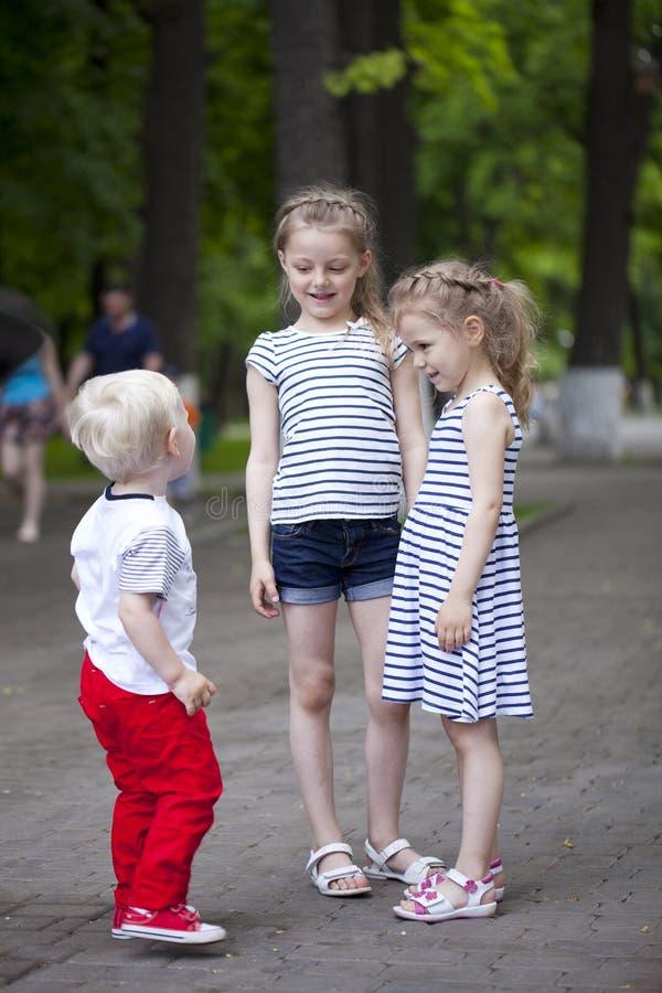 Rapaz pequeno e dois primos mais idosos, encontrando-se no parque do verão imagens de stock