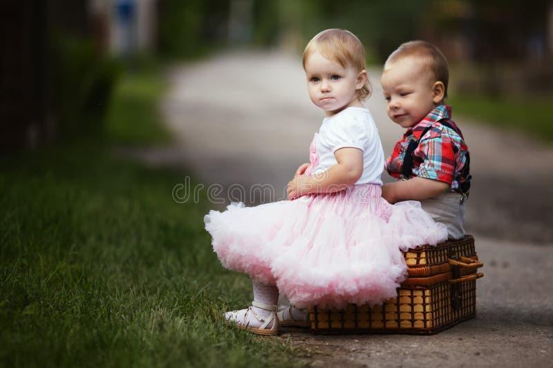 Rapaz pequeno e menina com mala de viagem imagens de stock royalty free