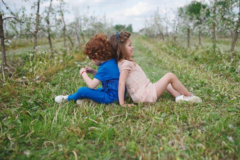Rapaz pequeno e menina no jardim de florescência imagens de stock royalty free