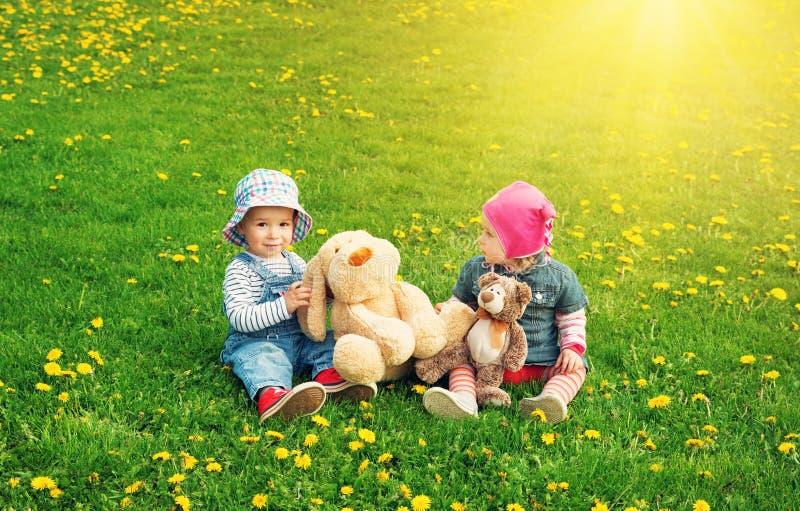 Rapaz pequeno e menina nos chapéus que sentam-se no campo com os brinquedos macios no verão imagem de stock royalty free
