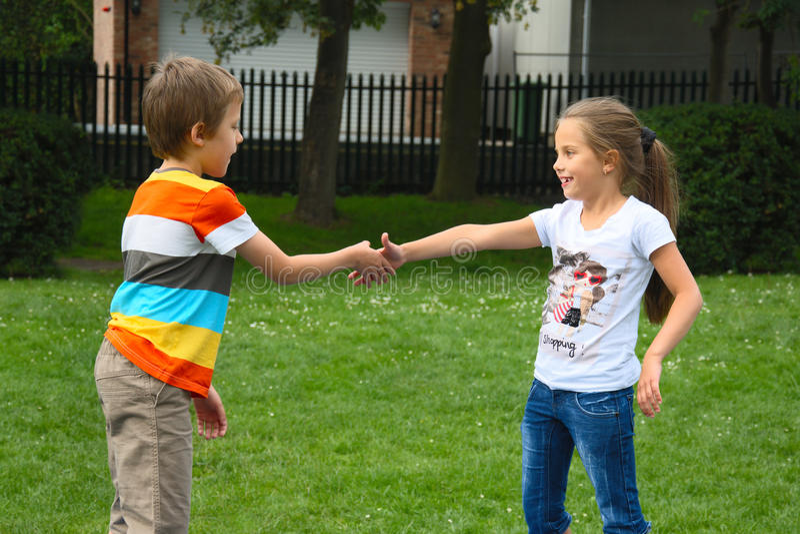 Rapaz pequeno e menina que agitam as mãos no parque, ao ar livre foto de stock