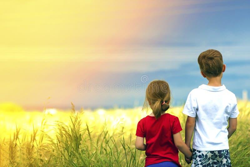 Rapaz pequeno e menina que estão guardando as mãos que olham no hor fotos de stock royalty free