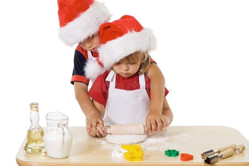 Rapaz pequeno e menina que fazem bolinhos do Natal imagem de stock